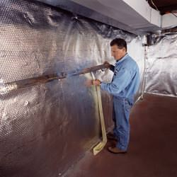 Installation of a radiant heat and vapor barrier on a basement wall in Hampton